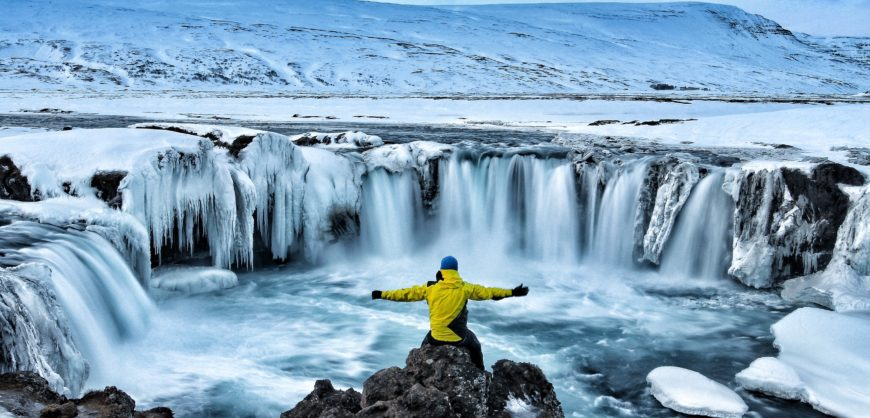 Hiker visiting Godafoss waterfall Iceland